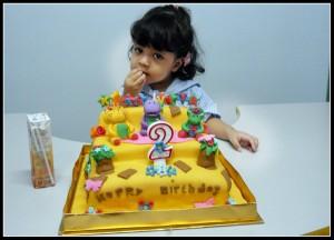 gadis kecil yang tidak sabar ingin memakan kue ulang tahunnya